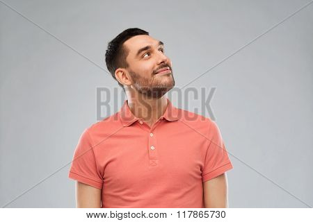 advertisement, idea, inspiration and people concept - happy smiling young man in polo t-shirt looking up over gray