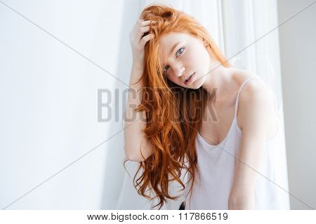 Sensual attractive young woman with beautiful long red hair standing near the window