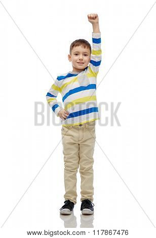 childhood, power, gesture and people concept - happy smiling little boy with raised hand