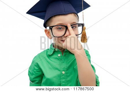 childhood, school, education, knowledge and people concept - happy boy in bachelor hat or mortarboard and eyeglasses