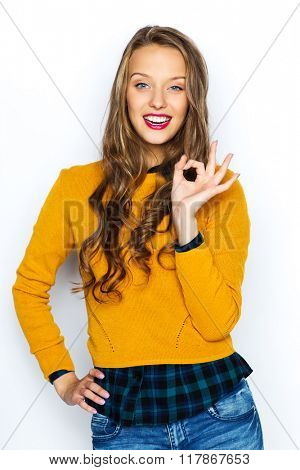 people, gesture, style and fashion concept - happy young woman or teen girl in casual clothes showing ok hand sign