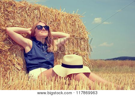 Woman resting on a bale of straw on the field