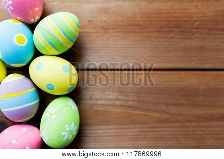 easter, holidays, tradition and object concept - close up of colored easter eggs on wooden surface with copy space