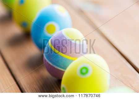 easter, holidays, tradition and object concept - close up of colored easter eggs on wooden surface