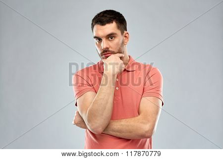 doubt, expression and people concept - serious man thinking over gray background