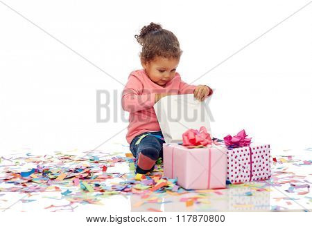childhood, birthday, party, holidays and people concept - happy smiling little african american baby girl with gift boxes and confetti playing with shopping bag sitting on floor