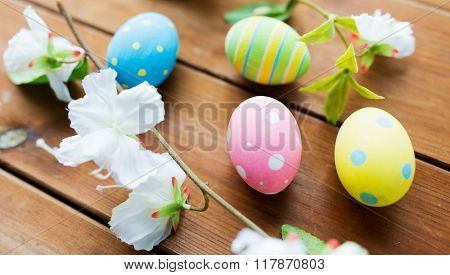 easter, holidays, spring, tradition and object concept - close up of colored easter eggs and flowers on wooden surface