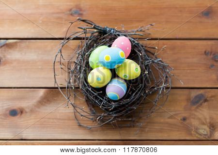 easter, holidays, tradition and object concept - close up of colored easter eggs in nest on wooden surface