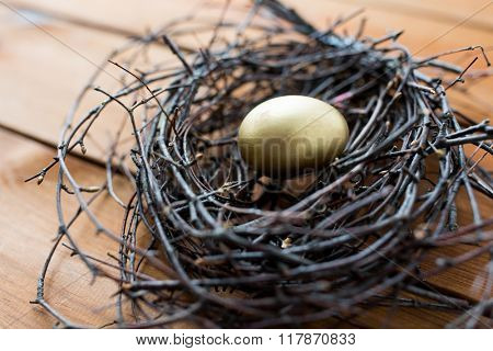 easter, holidays, tradition and object concept - close up of golden easter egg in nest on wooden surface