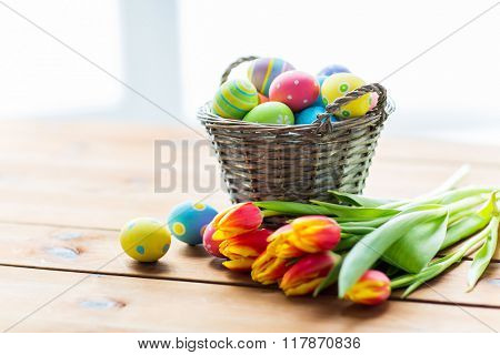 easter, holidays, tradition and object concept - close up of colored easter eggs in basket and tulip flowers on wooden table