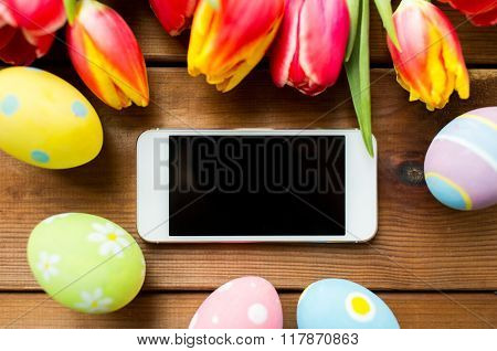 easter, holidays, tradition and object concept - close up of colored easter eggs, tulip flowers and smartphone with blank screen on wooden surface