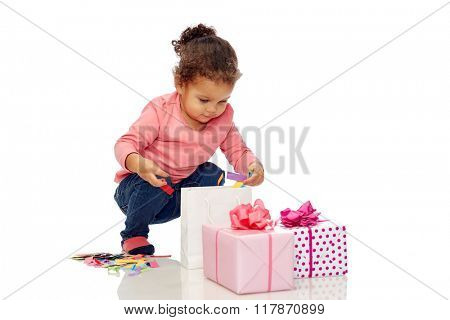 childhood, birthday, party, holidays and people concept - happy little african american baby girl with gift boxes playing with confetti and shopping bag