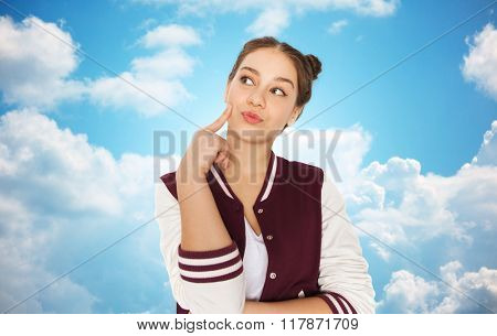 people and teens concept - happy pretty teenage girl thinking over blue sky and clouds background