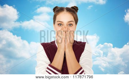 people, emotion, expression and teens concept - scared or confused teenage girl over blue sky and clouds background