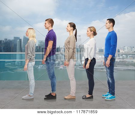 family, gender, high and people concept - group of men and women from side over singapore city waterside background