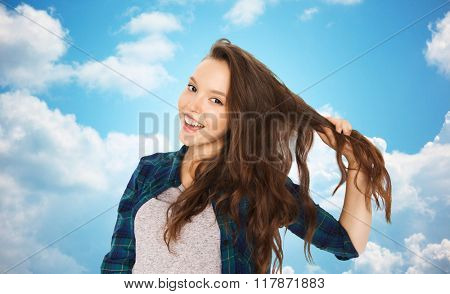 people, hair care, style and teens concept - happy smiling pretty teenage girl holding strand of her hair over blue sky and clouds background