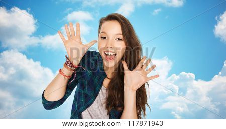 people and teens concept - happy laughing pretty teenage girl showing hands over blue sky and clouds background