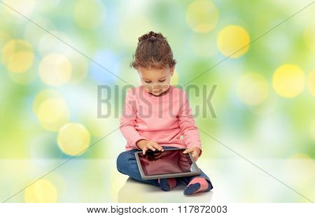 childhood, technology and people concept - little african american baby girl playing with tablet pc computer and sitting on floor