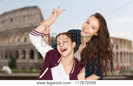 people, travel, tourism and friendship concept - happy smiling pretty teenage girls showing peace hand sign over coliseum in rome background