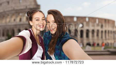 people, travel, tourism and friendship concept - happy smiling pretty teenage girls taking selfie over coliseum in rome background