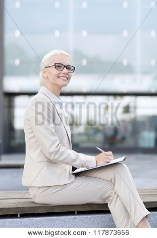business, people and education concept - young smiling businesswoman in glasses with notepad over office building