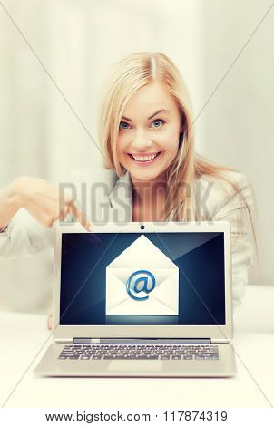 beautiful woman with laptop pointing at email sign