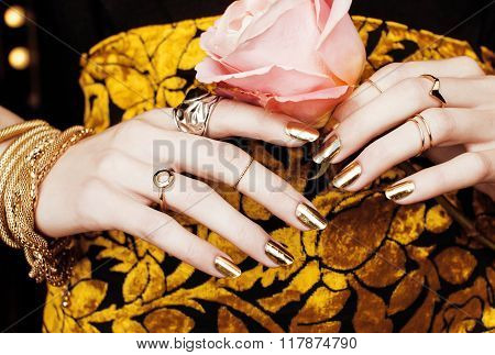 woman hands with golden manicure lot of jewelry on fancy dress close up