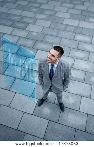 business, development, finances and people concept - young smiling businessman with forex chart on virtual screen outdoors from top