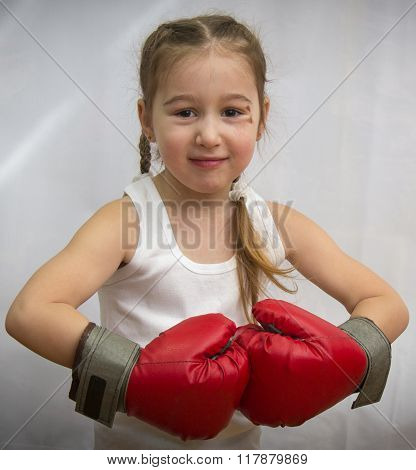 The little girl with pigtails and a bruise under the eye in boxing gloves