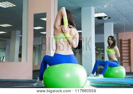 young woman doing exercise and stretching on a fitness ball
