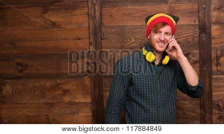 Hipster man speaking over mobile phone over wooden