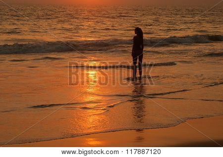 Sundown On Ocean Coast With Woman's Silhouette