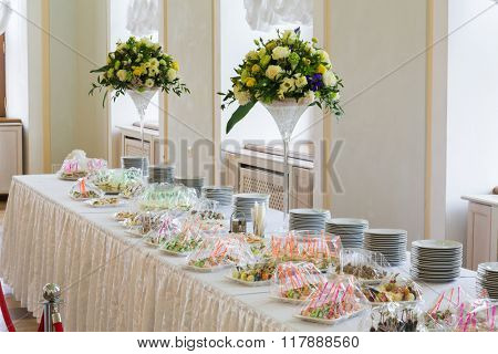 Cold table with many food and decorated flowers bouquet.