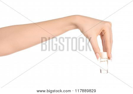 Perfume And Body Care Theme: Beautiful Female Hand Holding A Small Transparent Bottle Of Perfume On