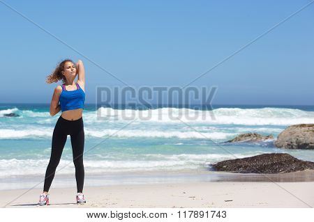 Sporty Young Woman Stretching At The Beach