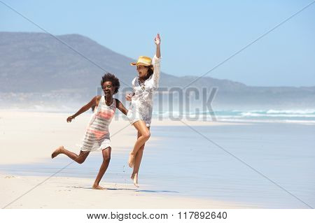 Carefree Young Women Walking Barefoot On Beach