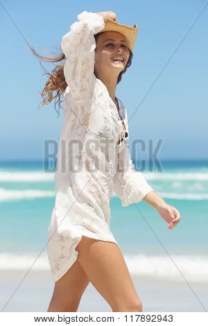 Smiling Woman Walking In White Summer Dress At The Beach
