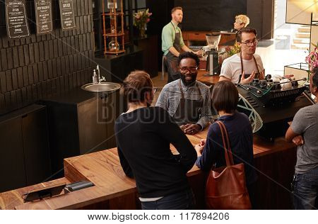 Smiling Afro-American barista assisting customers in a coffee sh