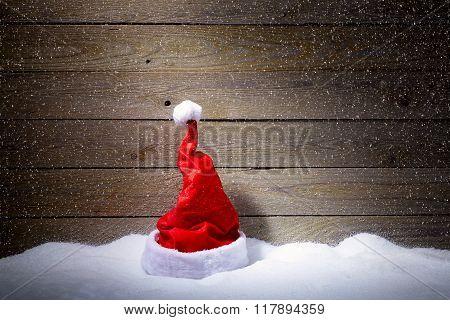 Lonley Santa Hat In Snow On Wooden Background