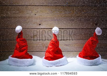 Santa Hats In Snow With Wooden Background