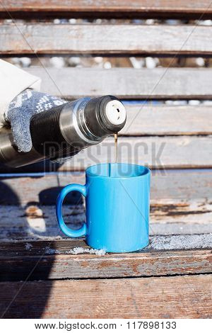 Woman Pouring A Hot Drink In Mug From Thermos