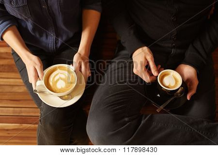 Hipster couple with cappucino and espresso from overhead