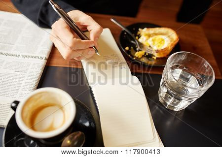 Person writing list at a cafe with coffee and pastry