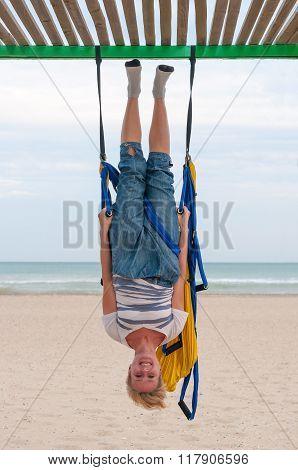 Anti-gravity Yoga, girl doing yoga exercises on the beach. Fly Yoga