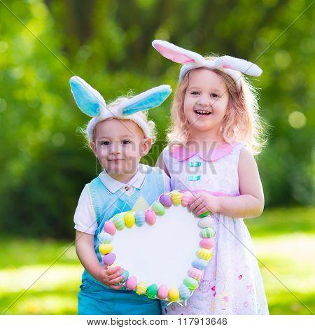 Little boy and girl having fun on Easter egg hunt.