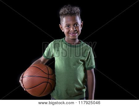 Cute young African American boy holding a basketball and ready to play. Future basketball star portrait