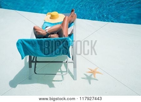 Woman in hat relaxation at private villa swimming pool sunbed