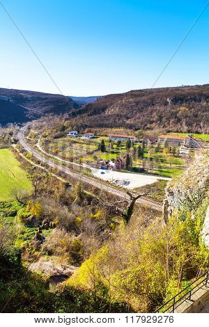 Countryside aerial view with railroad, mountains, houses and green field