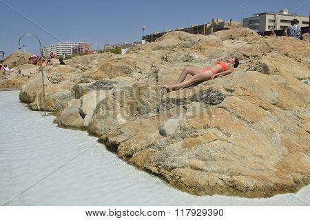 Woman Sunbathing On Rocks