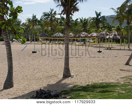 Beach With Volleyball Court And Tiki Shelters And Palm Trees